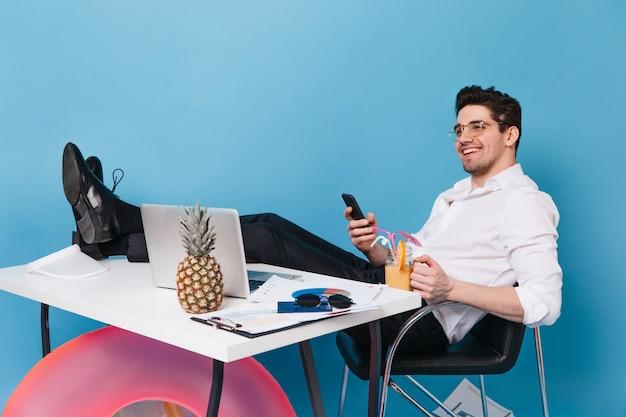 Homme souriant en chemise blanche et pantalon est assis avec ses jambes sur la table contre l'espace bleu. mec brune tenant le téléphone et un cocktail. employé posant avec ordinateur portable, ananas et cercle gonflable.