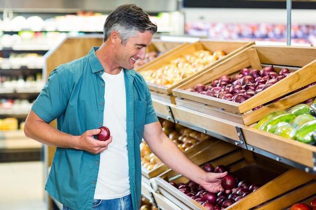Homme souriant choisissant un oignon