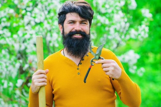 Homme souriant avec des ciseaux de jardin. travaux de jardinage au printemps.