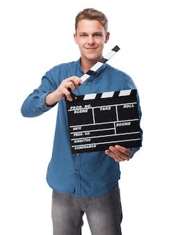Homme souriant avec un clapperboard