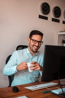 Homme souriant, communiquant avec ses collègues en ligne.