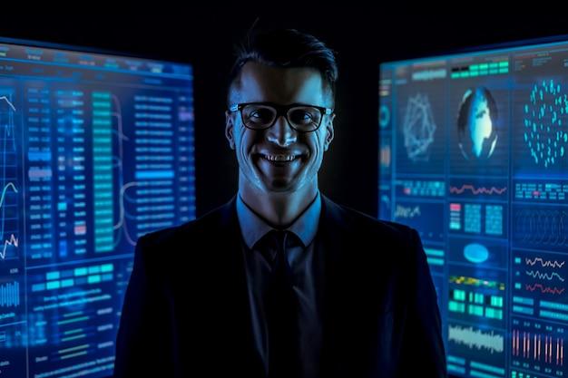 L'homme souriant en costume debout entre les moniteurs bleus dans une pièce sombre