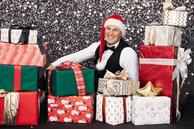 Homme souriant en costume portant un chapeau de père noël posant avec un cadeau de noël entouré de neige