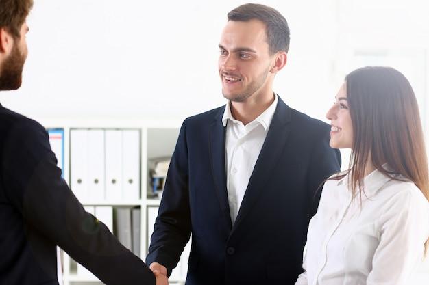 Homme souriant en costume se serrent la main comme bonjour au bureau