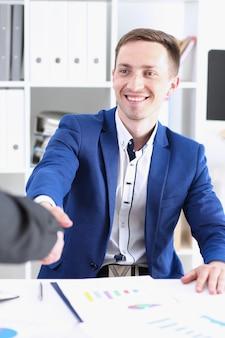 Homme souriant en costume, serrer la main comme bonjour dans le portrait de bureau. accueil d'un ami, offre de médiation, introduction positive, geste de salutation ou de remerciement, approbation de participation au sommet, concept de négociation de bras de grève