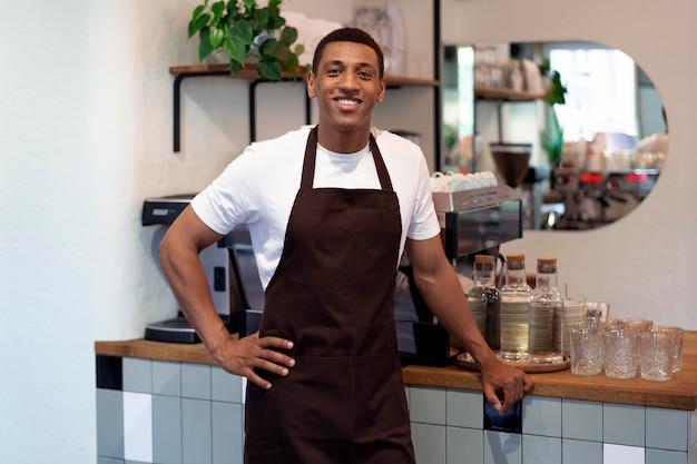 Homme souriant de coup moyen au café
