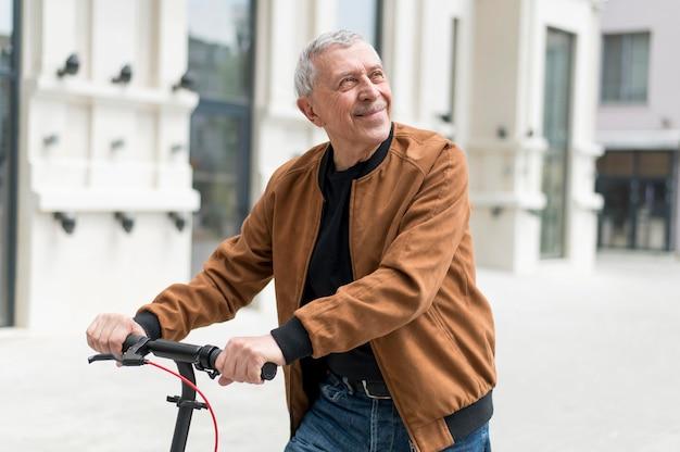 Homme souriant de coup moyen à l'extérieur