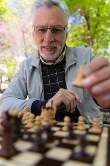Homme souriant de coup moyen jouant aux échecs