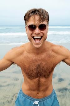 Homme souriant de coup moyen avec des lunettes de soleil