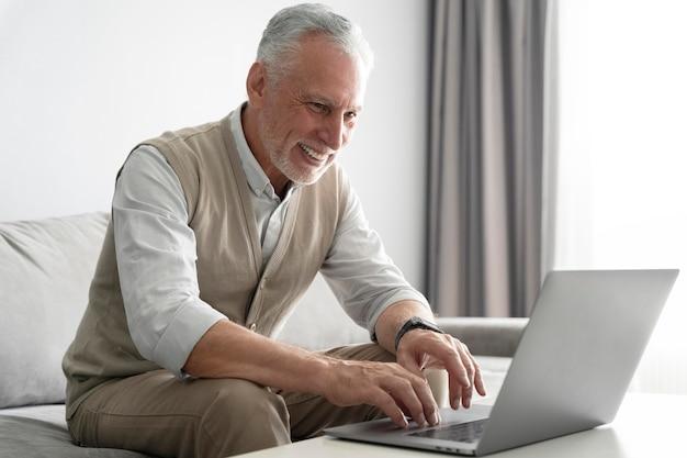Homme souriant de coup moyen avec ordinateur portable