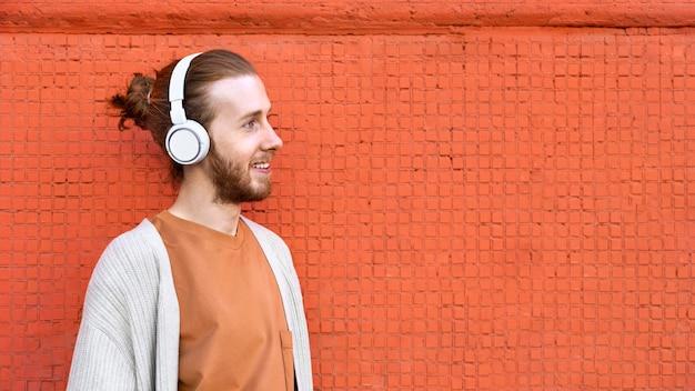 Homme souriant de coup moyen portant des écouteurs