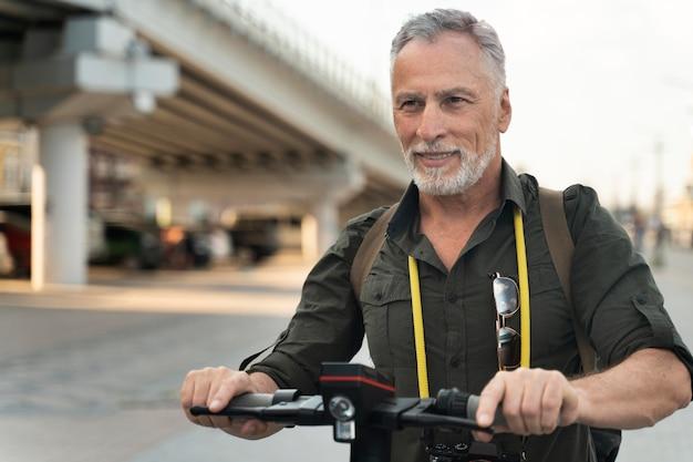 Homme souriant de coup moyen avec scooter