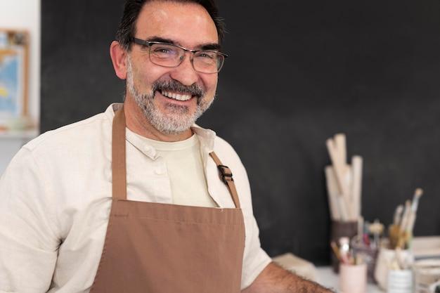Homme souriant de coup moyen avec tablier