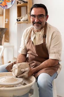 Homme souriant de coup moyen tenant de l'argile