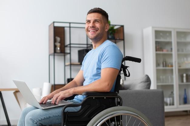 Homme souriant de coup moyen tenant un ordinateur portable