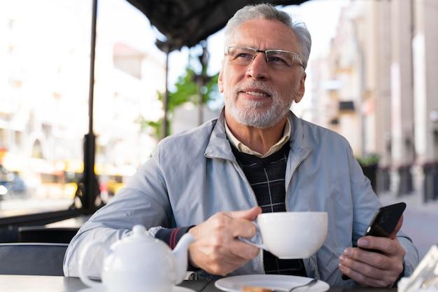 Homme souriant de coup moyen tenant un smartphone