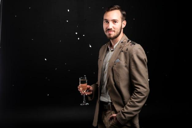 Homme souriant couvert de confettis tenant un verre de champagne