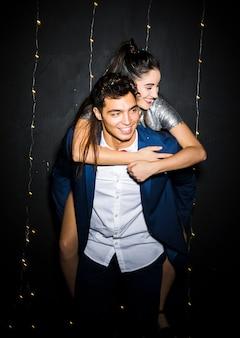 Homme souriant avec une dame heureuse sur le dos