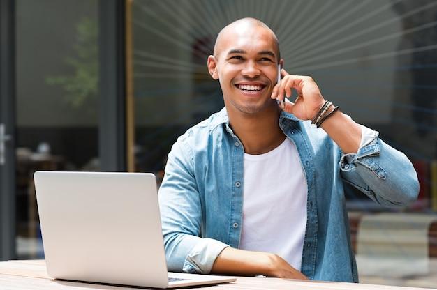 Homme souriant dans une conversation au téléphone en plein air