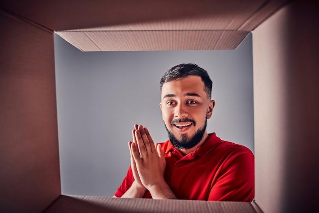 Homme souriant, déballant et ouvrant une boîte cadeau en carton, et regardant à l'intérieur. vue depuis la boite