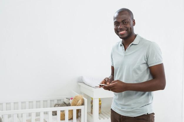 Homme souriant, debout à côté d'un berceau et messagerie texte sur téléphone portable à la maison