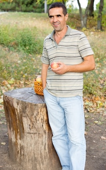 Homme souriant debout à côté d'un tronc d'arbre scié dans la campagne avec une pomme juteuse fraîche dans sa main