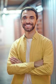 Homme souriant, debout dans une pièce éclairée