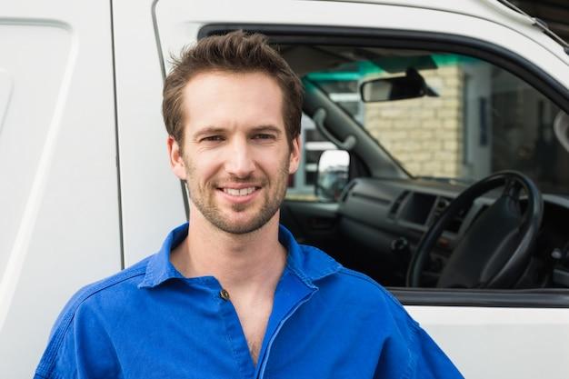 Homme souriant devant le camion de livraison