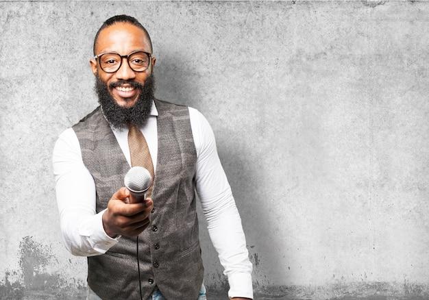 Homme souriant donnant un microphone