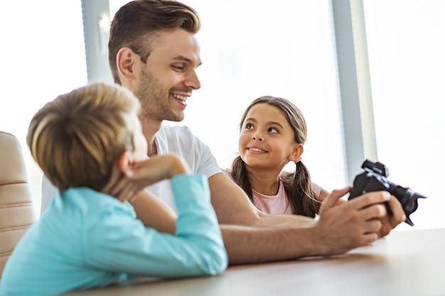 L'homme souriant avec des enfants tenant un appareil photo au bureau