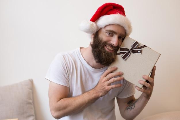 Homme souriant essayant de deviner ce qu'il y a à l'intérieur d'une boîte cadeau de noël