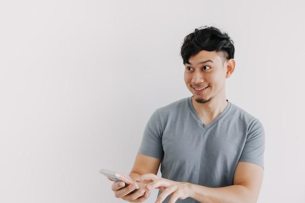 L'homme souriant est satisfait de l'application pour smartphone isolée sur un mur blanc