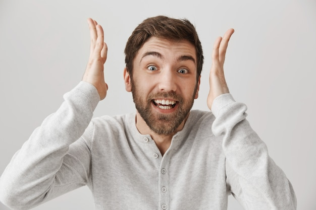 Un homme souriant excité réagit à des nouvelles incroyables
