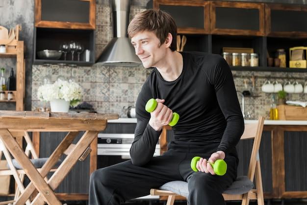 Homme souriant exerçant avec des haltères