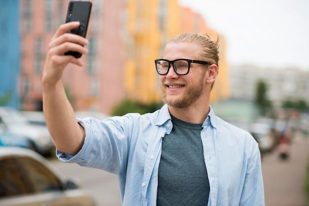 Homme souriant à l'extérieur en prenant un selfie
