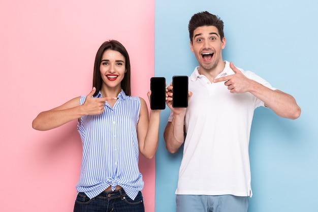 Homme souriant et femme en tenue décontractée debout et tenant des téléphones cellulaires, isolés sur un mur coloré