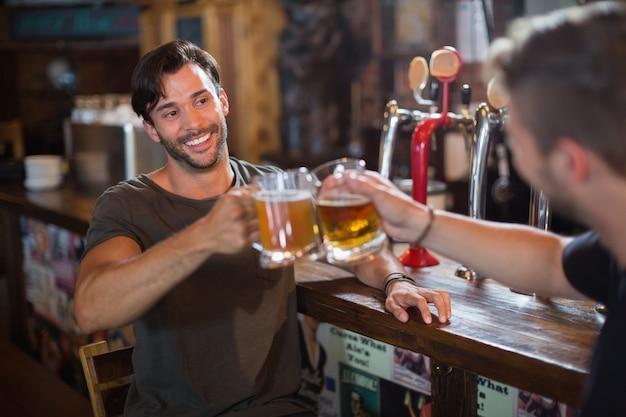Homme souriant, grillage, chope de bière avec un ami masculin