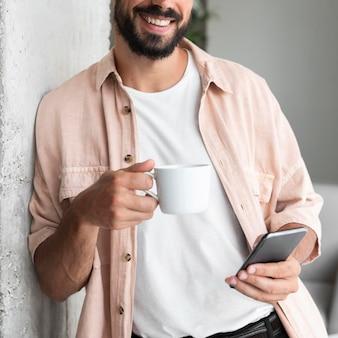 Homme souriant gros plan avec smartphone
