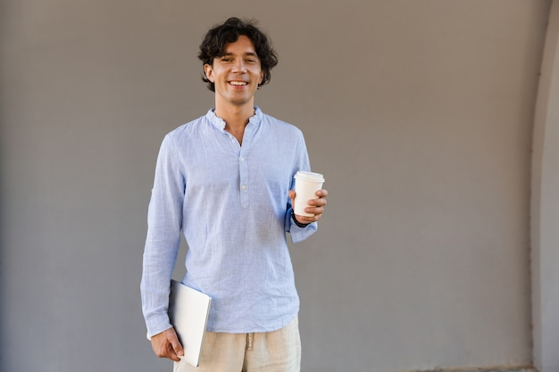 Homme souriant, habillé en chemise, boire du café
