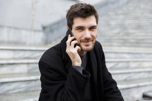 Homme souriant habillé en manteau assis dans la rue de la ville, parler au téléphone mobile
