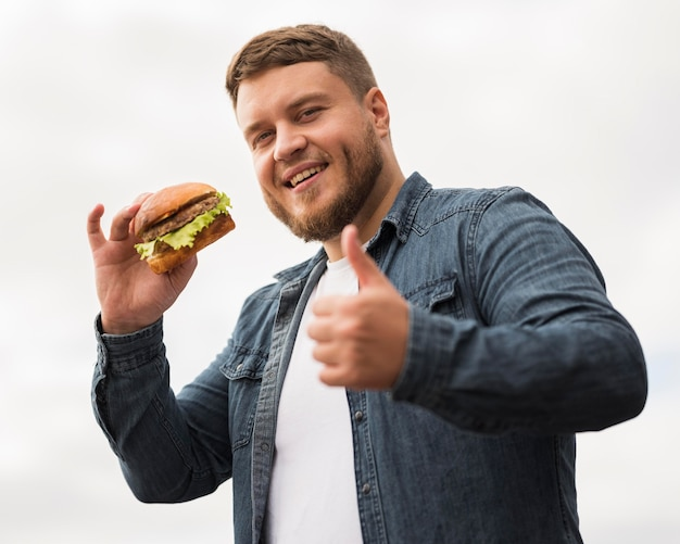 Homme souriant avec hamburger montrant l'approbation