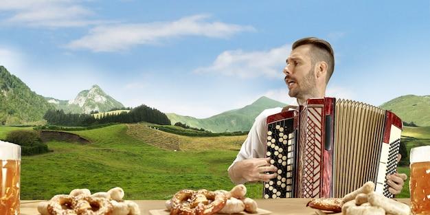 L'homme souriant heureux avec de la bière vêtu d'un costume traditionnel autrichien ou bavarois