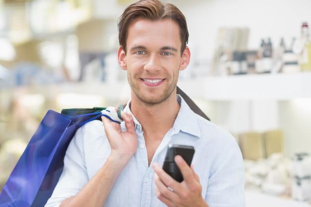 Un homme souriant heureux en regardant le téléphone au centre commercial