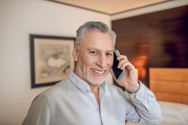 Homme souriant. homme d'affaires aux cheveux gris d'âge moyen souriant parlant au téléphone et ayant l'air satisfait