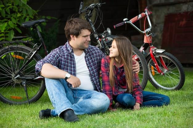 Homme souriant et jeune fille se reposant sur l'herbe après avoir fait du vélo