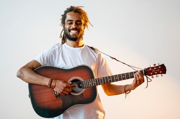 Homme souriant jouant de la guitare