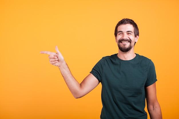 Un homme souriant et joyeux pointant vers sa droite sur le fond disponible pour votre publicité ou votre promotion. isolé sur fond orange en studio.