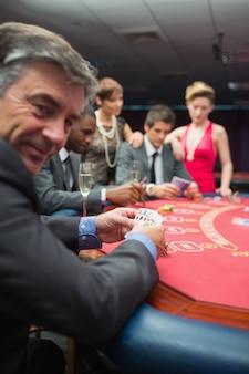 Homme souriant en levant du jeu de poker
