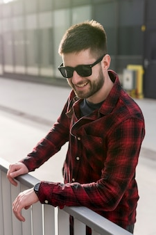 Homme souriant avec des lunettes de soleil se penchant sur la clôture