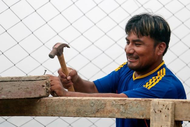L'homme souriant a un marteau dans sa main droite et est sur le point d'enfoncer un clou dans un morceau de bois